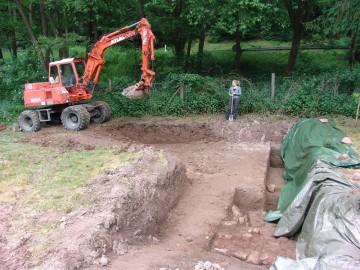 Der Bagger des Heimbuchenthaler Bauhofs gräbt das oberste Erdreich ab.