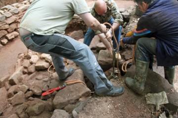 Die in den Brunnen gefallenen Wandungssteine lassen sich nur im Team bergen.