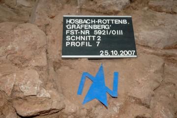Der blaue Nordpfeil gibt auf den Fotos eine Orientierungshilfe. Auf der Tafel sind die für die Grabung wichtigen Daten zu sehen.