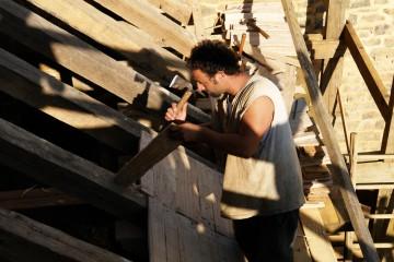 """Beim Bau der Burg im französischen Guédelon greift man alte Handwerkstechniken wieder auf. So darf es nicht verwundern, wenn die Latten auf dem Dachstuhl mit - natürlich handgeschmiedeten - Nägeln festgehämmert werden. Ähnlich dürften die Dächer der Fachwerkgebäude auf dem """"Alten Schloss"""" in Kleinwallstadt beschaffen gewesen sein."""