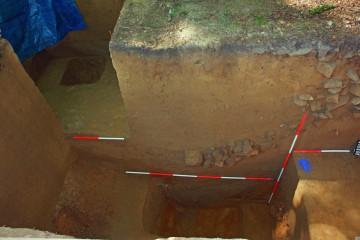 Im Grabenprofil zeichnet sich die Krone der ursprünglich etwa 15m hohen Ringmauer ab. Als diese in sich zusammenbrach, hatte sich der Graben bereits bis zur Hälfte mit Lehm gefüllt.