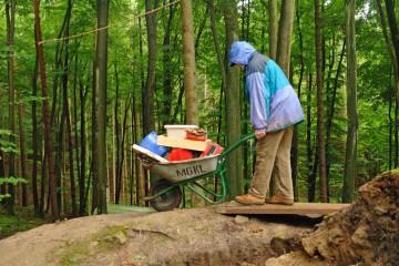 """""""Hab' mein' Wagen vollgeladen...."""". Gute Balance ist nötig, um die Grabungsutensilien sicher über die Planke und den Hang hinab zu transportieren. Dabei ist der Boden glatt wie Schmierseife."""