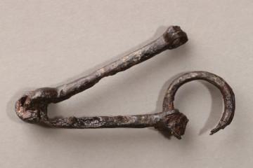 Die Funktion dieses Eisenobjektes hat sich erst nach dessen Restaurierung erschlossen. Die vorläufige Vermutung, dass es sich um Teile einer kleinen, eisernen Schnellwaage handelt, bestätigte sich nicht. Vielmehr stellen die einstmals beweglichen Eisenteile eine Pferdetrense dar, von der lediglich der zweite Ring fehlt.
