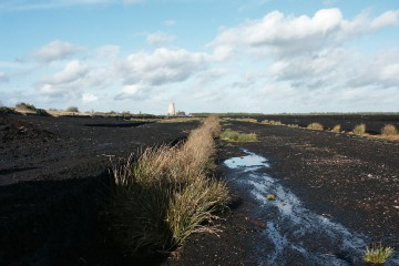 Torfabbau in der Nähe von Dowris (IRL). Im Hintergrund erkennt man ein modernes Heizkraftwerk.