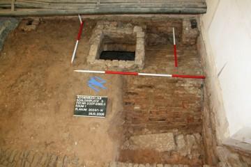 Der Keller in Raum 1. Deutlich zu erkennen ist der aus Backsteinen gesetzte Einstiegsschacht und das ebenfalls aus Backsteinen bestehende Tonnengewölbe.