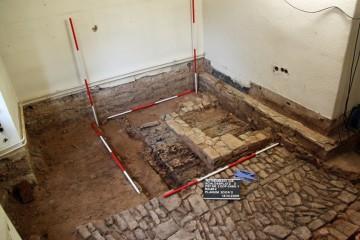 In Raum 2 befand sich unmittelbar neben dem steinernen Pflaster eine Herdstelle. Braune Verfärbungen zeigen, dass diese über einem hölzernen Dielenboden errichtet worden war.
