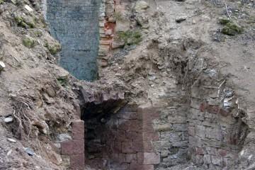 """Die Mauerreste des ehemaligen Kalkbrennofens am """"Hühnerlöchlein"""", der bis 1952 in Betrieb war, sind heute noch zu sehen. Die Steine wurden am Klettenberg, Zamesloch und anderen Steinbrüchen gebrochen, in einem Rundofen aufgeschichtet und gebrannt."""