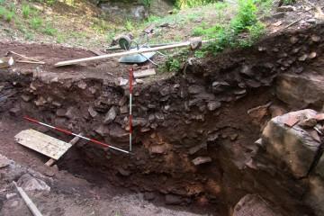 Stück für Stück wird der dichte Mauerversturz im Graben dokumentiert.