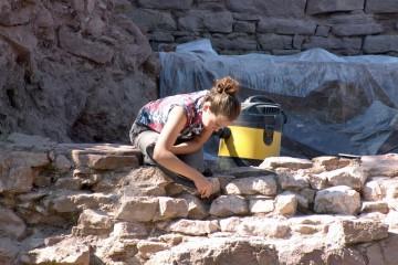 Auch eine Grabung braucht Pflege. So kommt beim Putzen der Mauer auch ein Staubsauger zum Einsatz.
