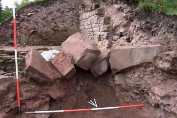 Die bossierten äußeren Ecksteine der Ringmauer liegen noch so im Torbereich, wie sie beim Abriss der Burg im 17. Jahrhundert zu Boden gefallen sind.