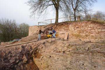 Die Säuberung des Zwingers macht Fortschritte. Bald schon können die an dieser Stelle erhaltenen Reste der Ringmauer für die Nachwelt dokumentiert werden. Stets im Einsatz: Die neuen, knallgelben Schubkarren. Der Anstrich erlaubt es nun auch allen Partensteinern ohne Feldstecher, am Voranschreiten der Grabung zumindest visuell Anteil zu nehmen.
