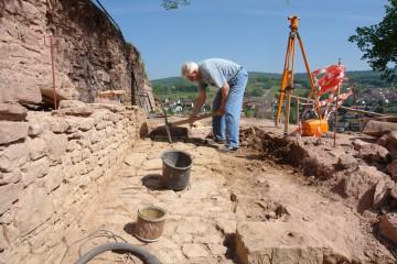 Am letzten Grabungstag wird die Mauer und das Pflaster davor nochmals für das Foto hergerichtet.