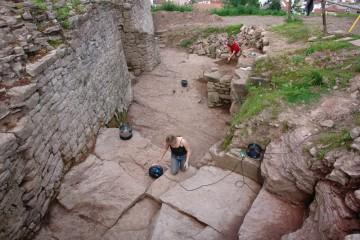 Während Gergely im Hintergrund noch Steine von grobem Dreck befreit, richtet Nina den Burggraben mit dem Staubsauger für's Foto her.