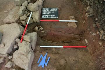 Grabungsfoto von Grab 3, Blick nach Norden. Deutlich zu erkennen ist der Ausbruch Kirchenmauer der Phase 1.