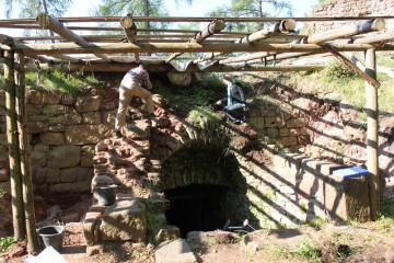 Vor der Dokumentation des Kellereingangs wird der Treppenschacht von Moos und Farnen befreit.
