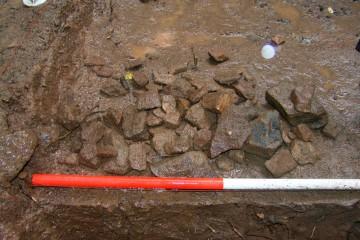 Dem Regen trotzend untersuchen wir das Areal neben dem Palas. Scharfkanitige Sandsteinsplitter ganz unterschiedlicher Abmessungen zeigen uns dabei, dass man ortsfremde Sandsteinblöcke erst auf der Burg zu Werksteinen zurichtete. Der Abfall verblieb zur Stabilisierung in des Bodens vor Ort.