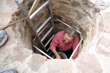 Im Brunnenschacht wird das Auflager für das eiserne Gitter neu befestigt.