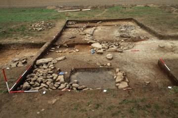 Die Bebauung in Schnitt 1/5 stellt sich als Fundamentmauern und Steinstückungen dar. Blickrichtung West.