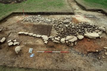 Die vorne rechts sichtbaren Reste eines Ofens werden von jüngeren Gebäudefundamenten überlagert. Blickrichtung Nord.