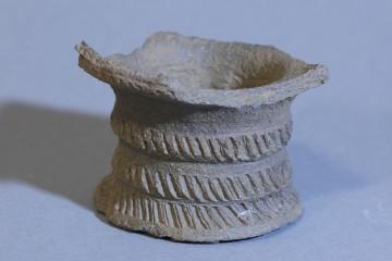 Fuß eines Bechers aus Protosteinzeug mit mehrzonigem Rädchendekor. Das Stück dürfte von einer Werkstatt in Südhessen hergestellt worden sein.