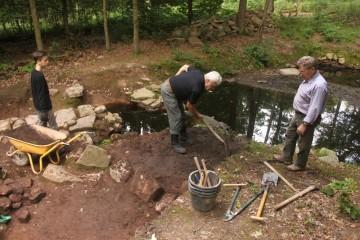 Die Uferzone ist mit Steinen befestigt - schwieriges Grabungsterrain für Marius, Waldemar und Ingbert.