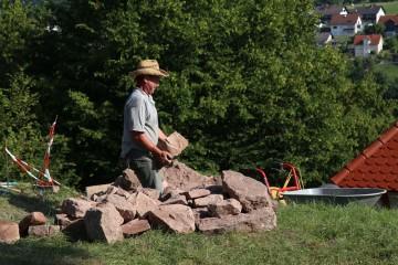Rüdiger lädt Mauersteine auf seinen elektrischen Schubkarren.