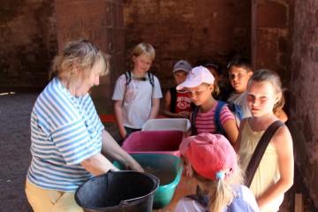 Annelie zeigt Weilbacher Schülern die frisch gewaschenen Funde.