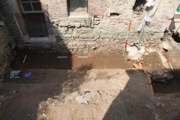 In der Grabungsfläche zeichnete sich eine mit Brandschutt verfüllte Grube eines hölzernen Vorgängerhauses ab ...