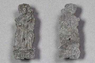 Fragment eines Pilgerzeichens mit stehender Madonna von der Burg Bartensten, Blei, um 1300, Partenstein, Museum Ahler Kram, Fd.-Nr. 2251, H. 4,9 cm, Br. 2,0 cm