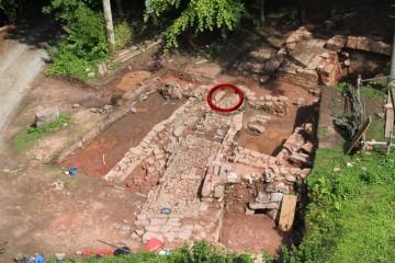 Das Fragment der Prophyrplatte lag in der Unterfütterung eines gepflasterne Weges nördlich des Klosterareals (roter Kreis).