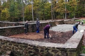 Handarbeit: Verteilen der Schotterschicht auf dem wiederverfüllten Friedhofsareal