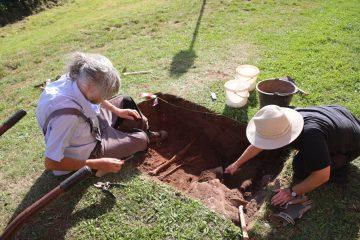 Sondage … und Treffer. Südlich der Kirche stießen wir bereits knapp unter der Grasnabe auf Bestattungen.
